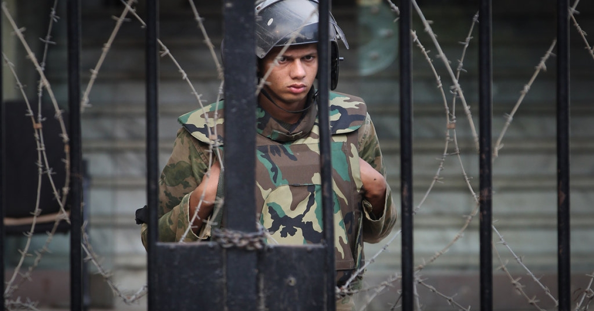 A soldier watches as protestors stage a sit-in outside the government cabinet office on November 26, 2011 in Cairo, Egypt. Thousands of Egyptians are continuing to occupy Tahrir Square ahead of parliamentary elections to be held on November 28.</p>