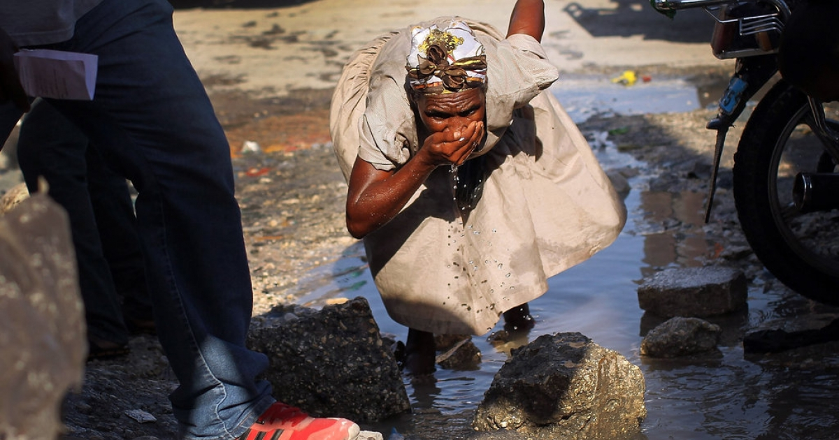 A woman drinks water in the street on March 6, 2012 in Port-au-Prince, Haiti. Two years after the 7.0 magnitude quake that killed an estimated 316,000 people, much of Haiti is still in a crisis situation with tens of thousands living in tent camps in and around Port-au-Prince. A growing concern to international donors is a flare-up between ex-members of Haiti's armed forces and the current Haitian President Michel Martelly.</p>