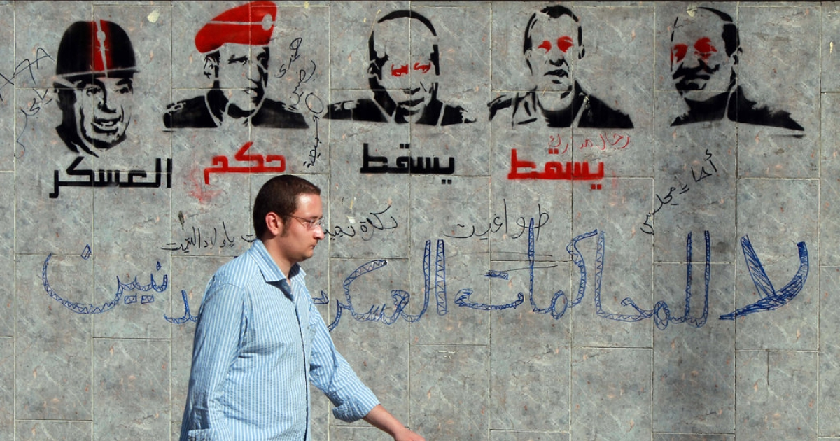 An Egyptian man walks past graffiti depicting members of the military council and reading 'Down with the military rule, no to military trials for civilians' near the defense ministry in the Abbassiya district of Cairo on April 29, 2012.</p>