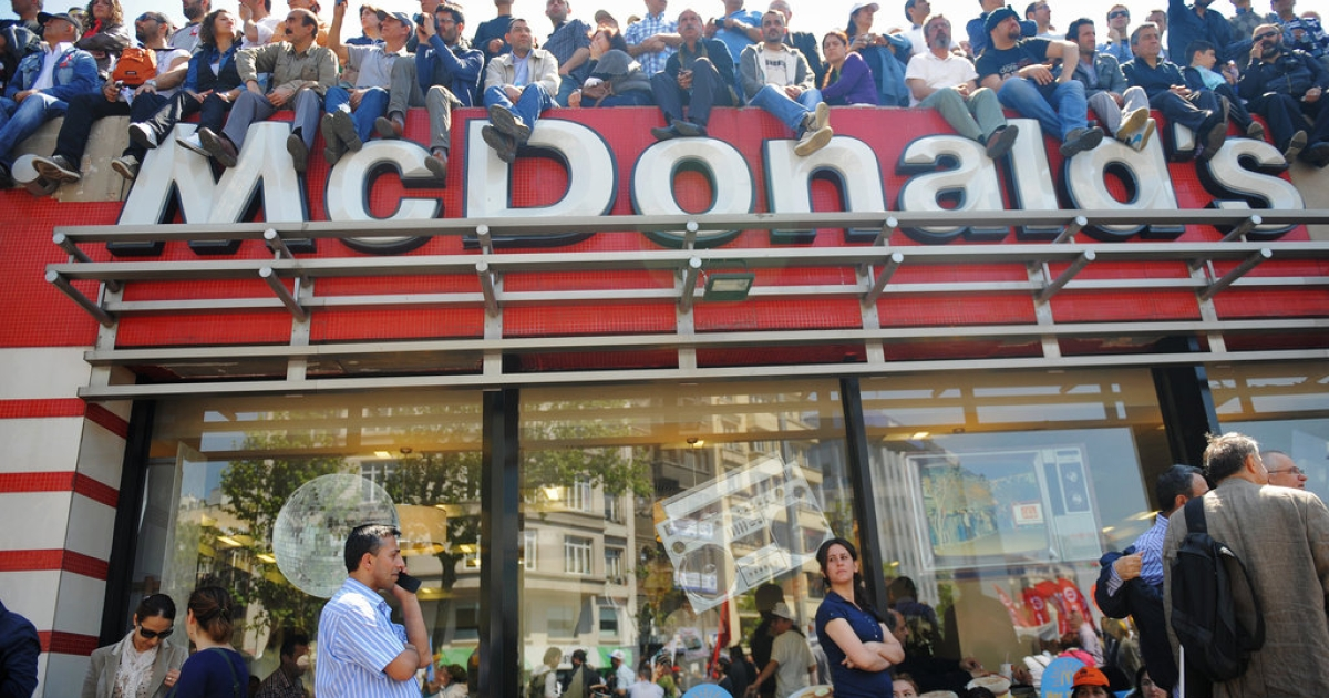 People sit on top of a McDonald's restaurant to watch a May Day rally in central Istanbul on May 1, 2012. Tens of thousands of workers gathered on an iconic square in the heart of Turkey's biggest city to observe the holiday, also known as International Workers' Day.</p>
