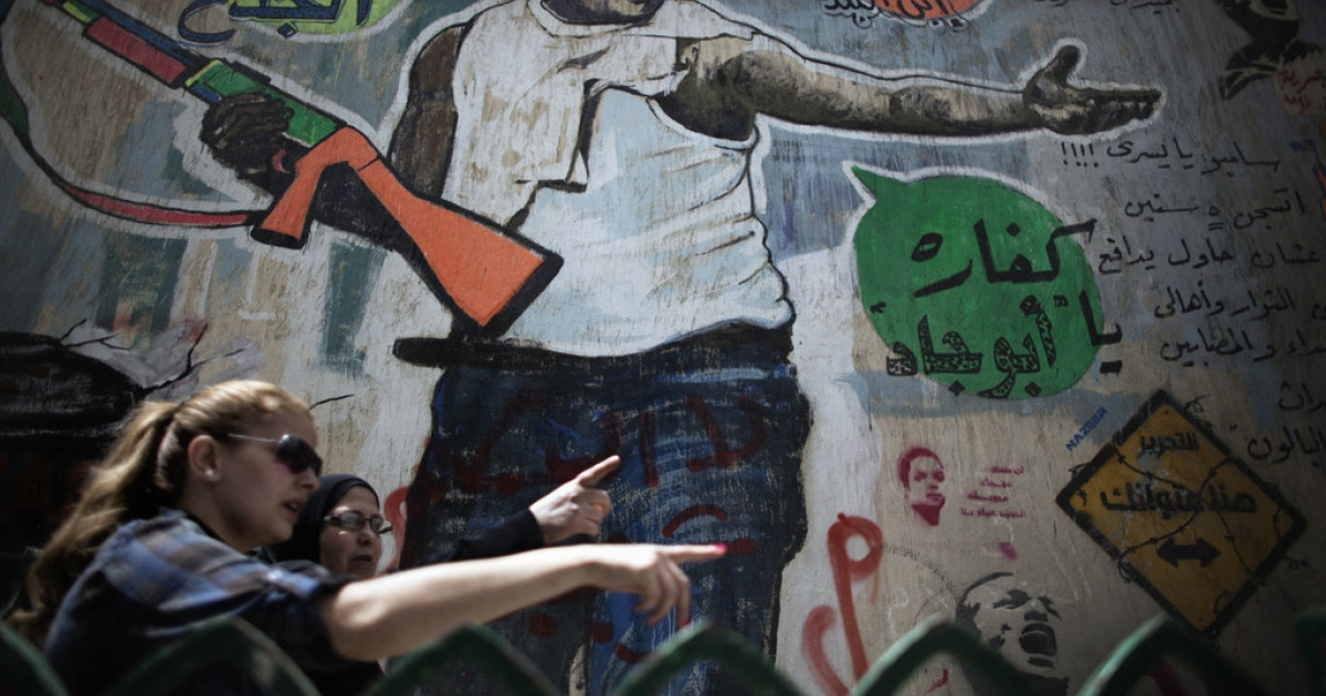 Egyptian women walk in front of a wall with revolutionary graffiti near Cairo's Tahrir Square on May 22, 2012, one day before the country's landmark presidential elections.</p>