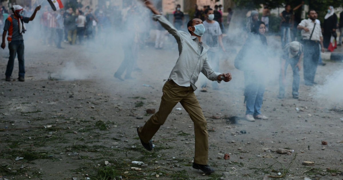 Egyptian protesters throw stones towards riot police during clashes near the US Embassy in Cairo on September 13, 2012.</p>