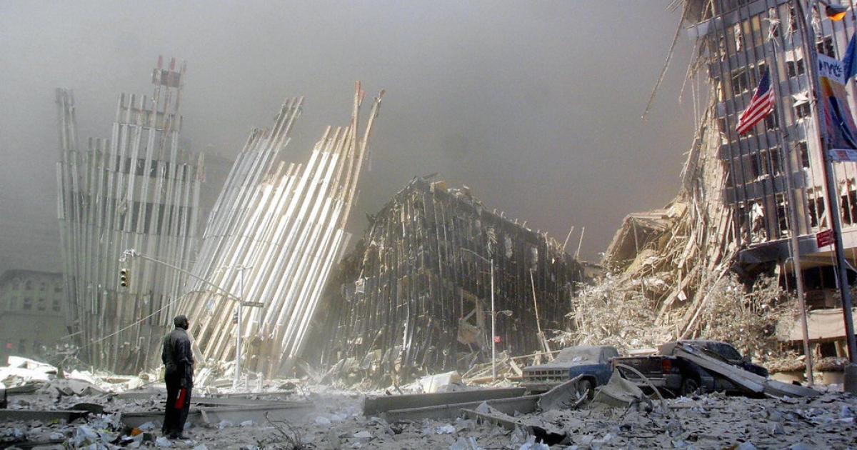 A man stands in the rubble of the north tower of the World Trade Center in New York City, calling out to potential survivors.</p>