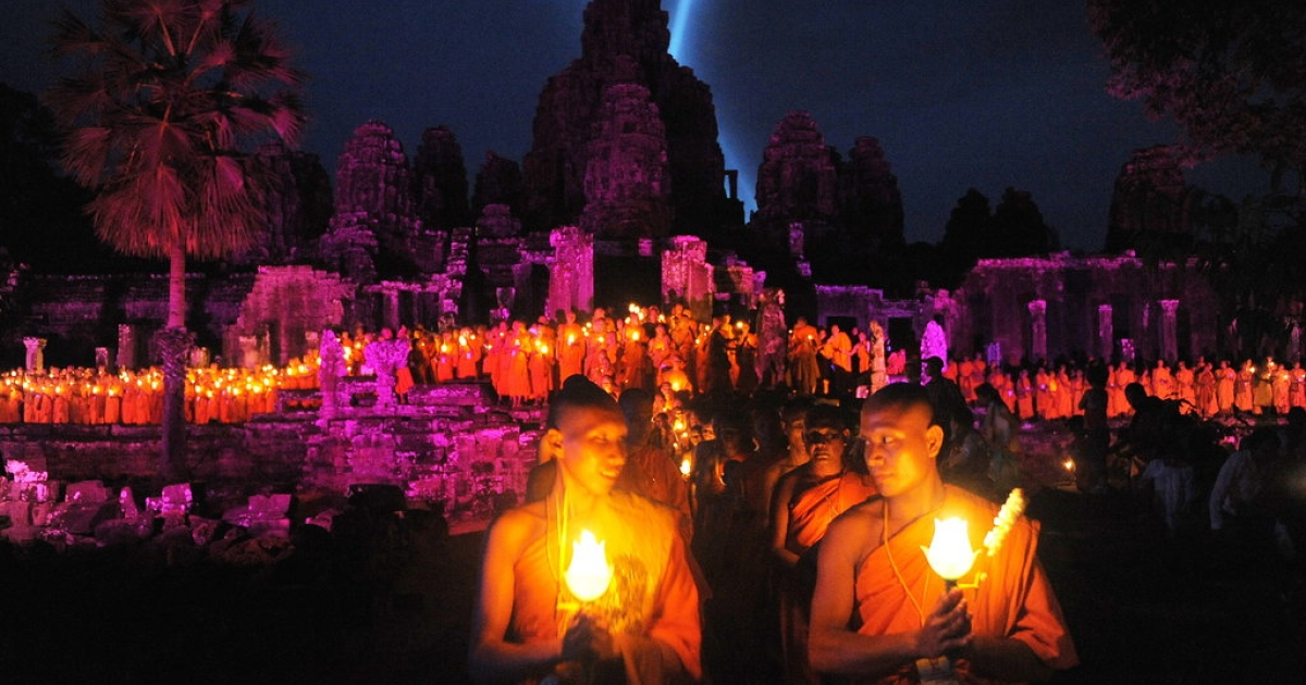 Cambodian Buddhist monks walk with lighted candles at Bayon temple during the Visak Bochea —
