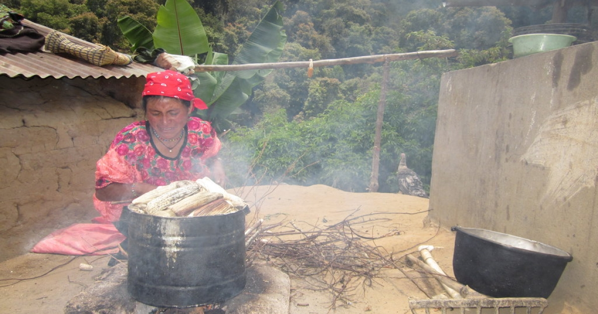 Maria Lucas Lopez, 52, makes tamales over a fire in Huetancito, Guatemala.</p>