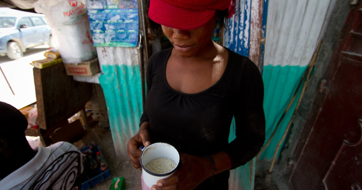 Elene Sainte Somé, 22, sells rice by the cup from her small shop in Coupon, located in Haiti's rice-growing Artibonite region. She says American rice sells better because it's processed to remove rocks and dirt.</p>