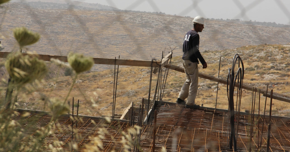 A Palestinian worker frames a house in the Israeli settlement of Nili.</p>