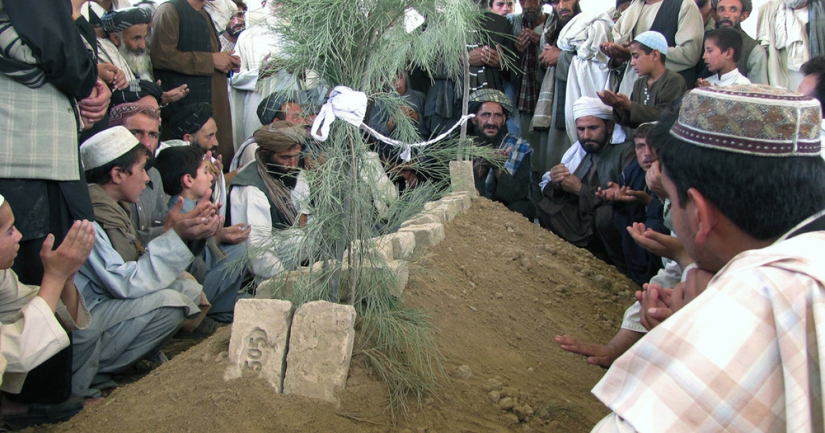 Mourners prayed over the grave of Ahmad Wali Karzai, the brother of Afghan president Hamid Karzai, during a funeral in Kandahar province on July 13, 2011. At a mourning ceremony for Karzai the following day, a suicide bomber killed Kandahar's supreme government religious authority and at least two other people.</p>