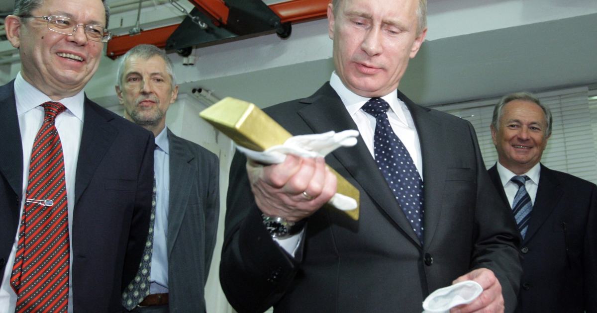 Russian PM Vladimir Putin holds a gold bar while visiting the Bank of Russia.</p>