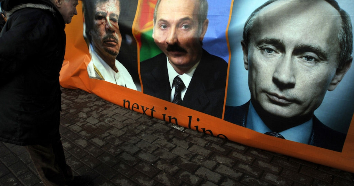 A man looks at a banner with portraits of (left to right) Libyan leader Muammar Gaddafi, Belarus President Alexander Lukashenko, Russian Prime Minister Putin and a sign reading