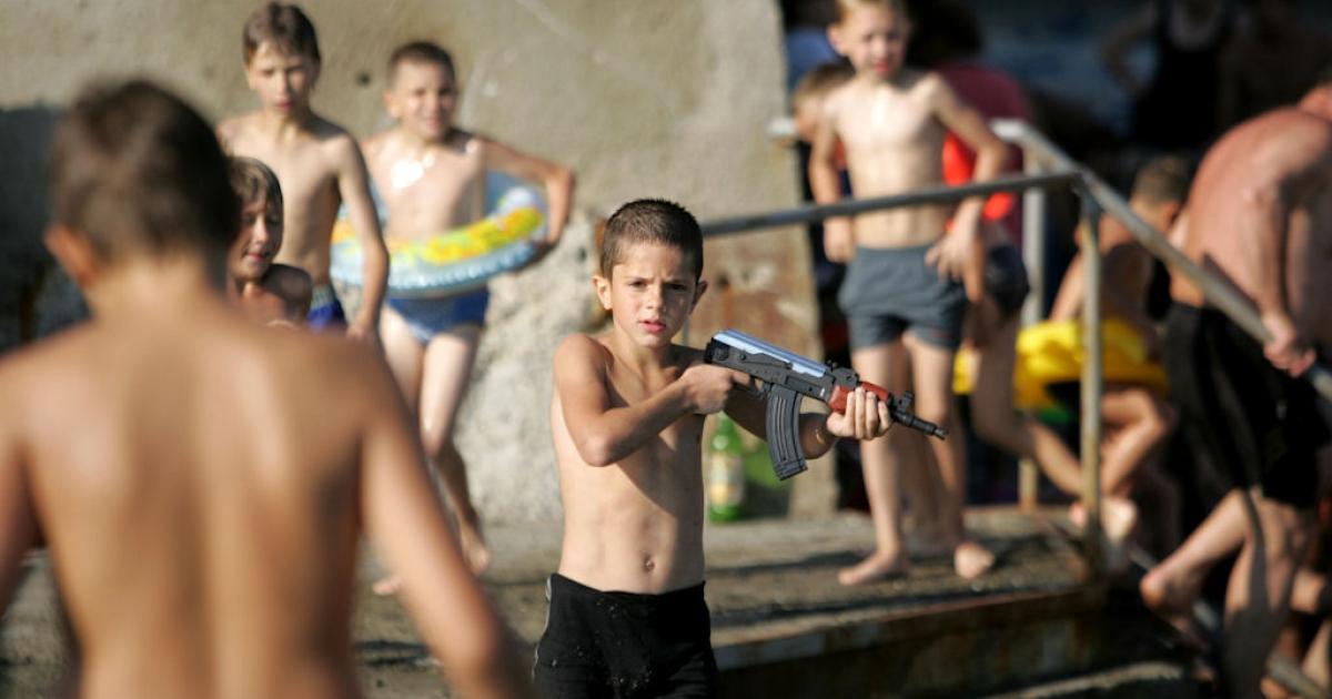 A boy plays with a toy Kalashnikov rifle at a public beach in Sochi, Russia on July 3, 2010.</p>