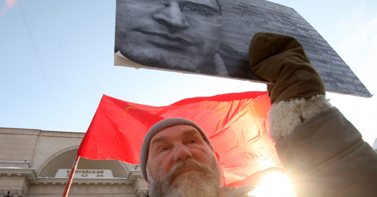 A man holds a portrait of the jailed former head of the Yukos oil giant Mikhail Khodorkovsky as left opposition activists take part in the so called 'Day of People's Rage' protest rally in St. Petersburg, on February 12, 2011.</p>