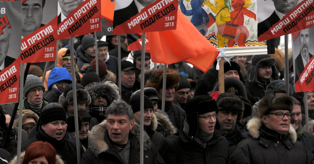 Russian opposition leaders (first row) Boris Nemtsov (2L), Vladimir Ryzhkov (2R) and Mikhail Kasyanov (1R) attend an opposition rally on January 13, 2013, in the center of Moscow against a Kremlin law that bans US adoptions of Russian orphans.</p>