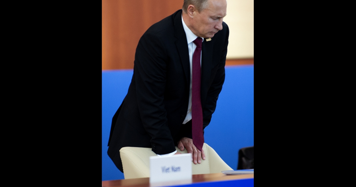 Russian President Vladimir Putin braces himself against his chair as he arrives to begin the Asian Pacific Economic Cooperation (APEC) Summit Leaders Retreat II in Vladivostok on September 9, 2012. The Kremlin has been trying to downplay rumors of Putin's health, specifically his back problems.</p>