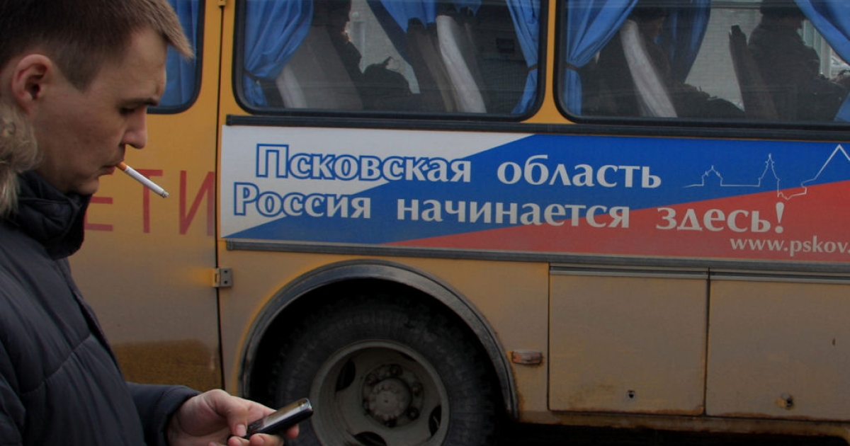 A bus in Pskov city with a banner that reads,