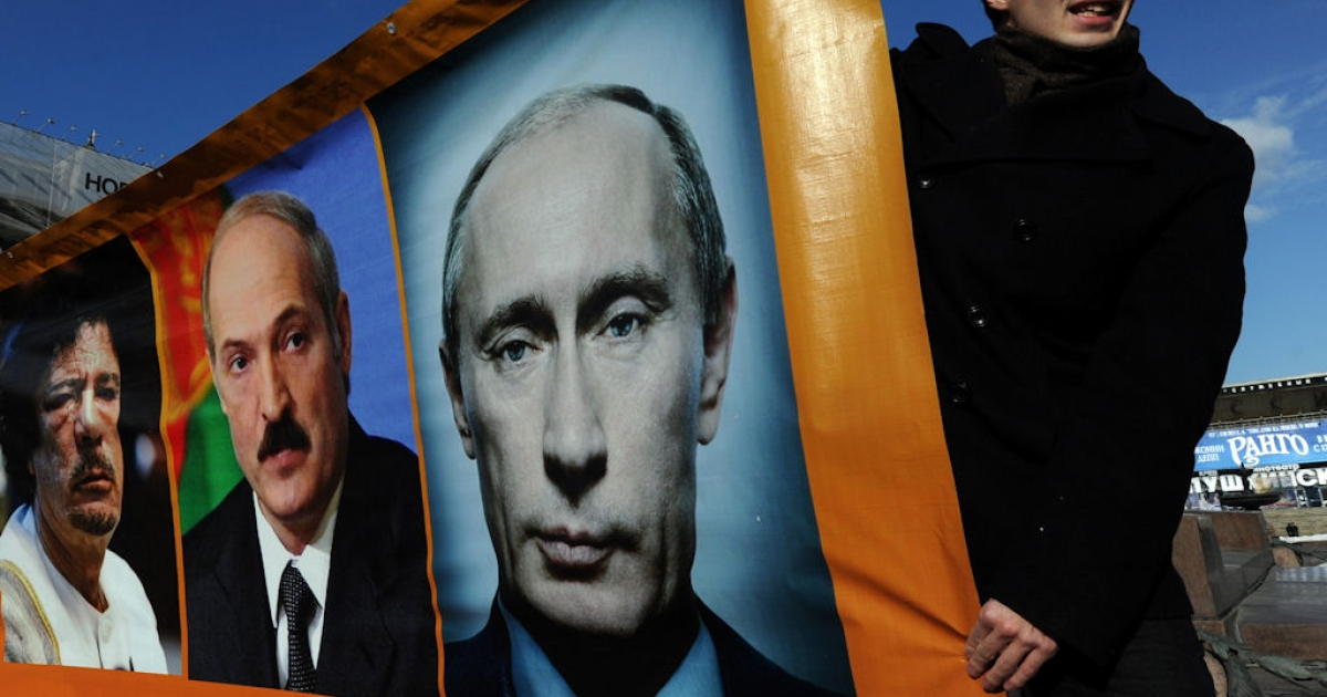 Opposition activists hold a banner with portraits of (left to right) Libyan leader Muammar Gaddafi, Belarus President Alexander Lukashenko and Russian Prime Minister Putin during an authorized rally at Pushkinskaya Square in Moscow, on March 13, 2011.</p>