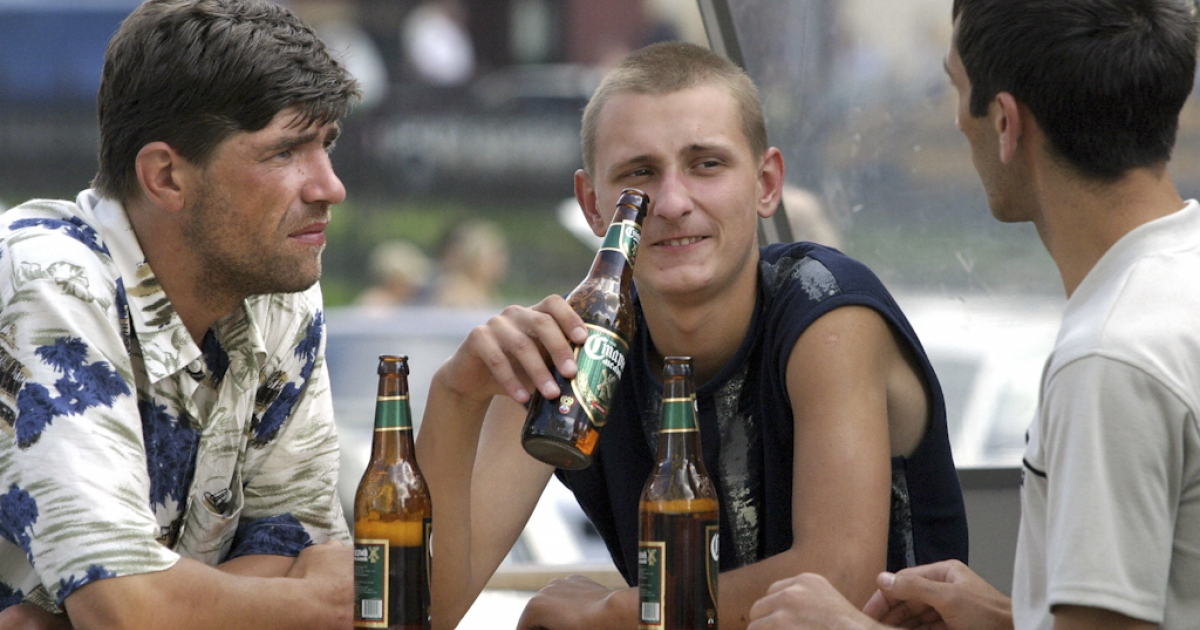 Three Russian men drink a beer in the open air snack-bar in Moscow. Russian President Dmitry Medvedev has signed a bill that officially classifies beer as alcoholic.</p>