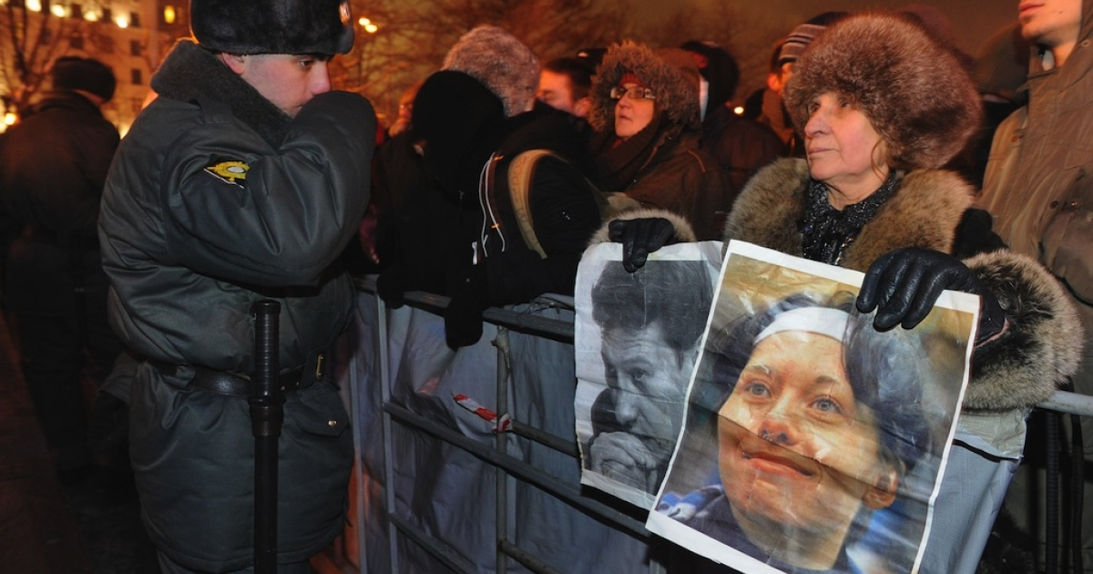 A woman holds portraits of slain lawyer Stanislav Markelov (L) and Russian journalist Anastasia Baburova (R) during a rally at the Pushkinskaya Square in central Moscow, on January 19, 2012.</p>