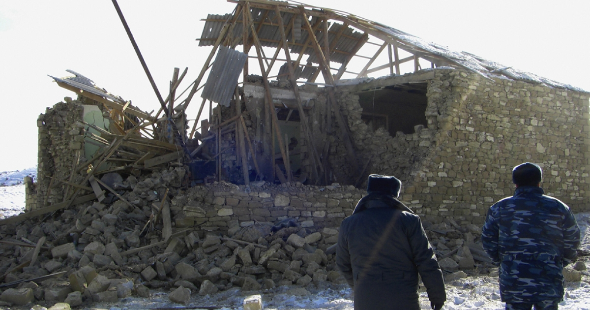 Russian troops look at a destroyed house located in the turbulent Dagestan region of North Caucasus.</p>