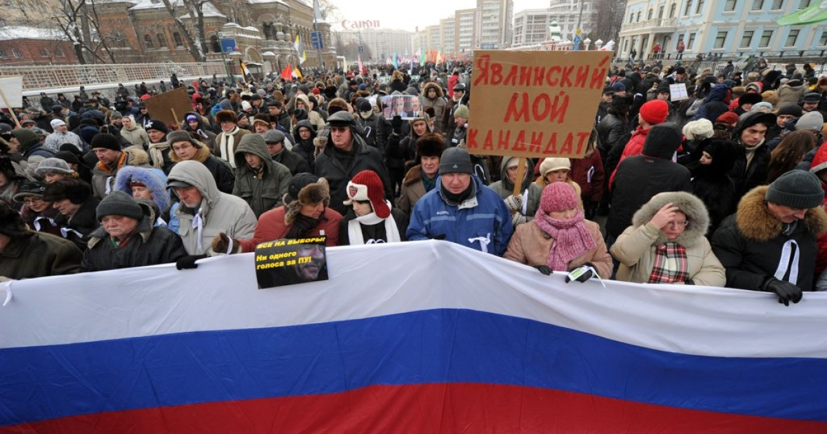 People carry a Russian flag as they march in a anti-Putin rally in central Moscow, on February 4, 2012. The poster reads: