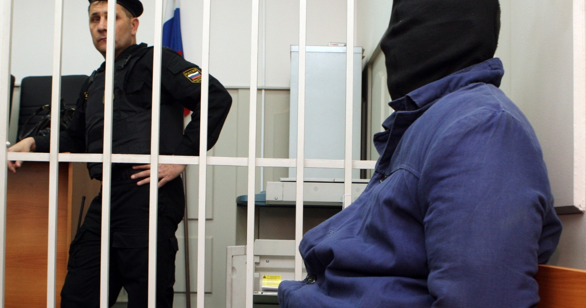Russian murder suspect Nikita Tikhonov, with a black bag over his head, sits in the defendant's cage of a Moscow court on Nov. 5, 2009. Two Russian nationalists, a man and a woman, Nikita Tikhonov and Yevgenia Khasis have been arrested and charged in the high-profile killings of human rights lawyer Stanislav Markelov and Anastasia Baburova, a reporter at opposition newspaper Novaya Gazeta, who were gunned down in Moscow in January.</p>