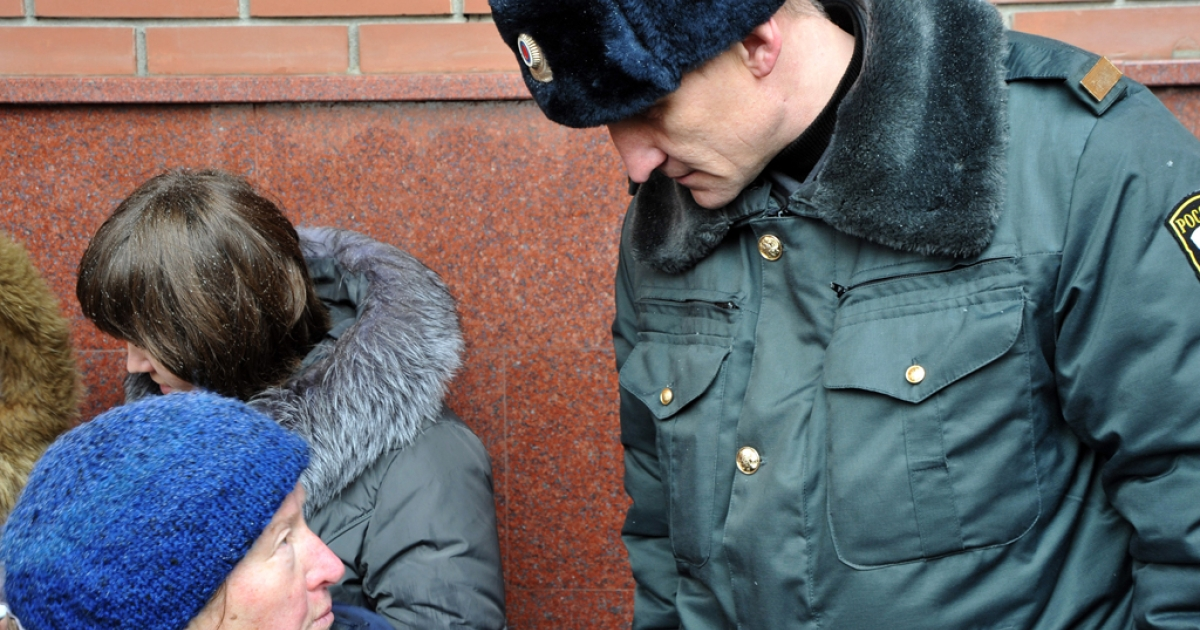 A police officers looks at a woman who calls herself a relative of police abuse sufferer outside the headquarters of the Investigative Committee's local department in Kazan, the capital of Tatarstan, on March 21, 2012, as she tries to lodge a complaint to investigators from Moscow. Russia's Investigative Committee is looking into local police violence in Tatarstan, a mostly Muslim region on the Volga River, after the shocking death of Sergei Nazarov, in Kazan on March 10 focused attention on brutal methods used on suspects. Officers of Kazan's police station allegedly raped  52-year-old Nazarov, a suspect in custody with a champagne bottle, leading to the man's death.</p>