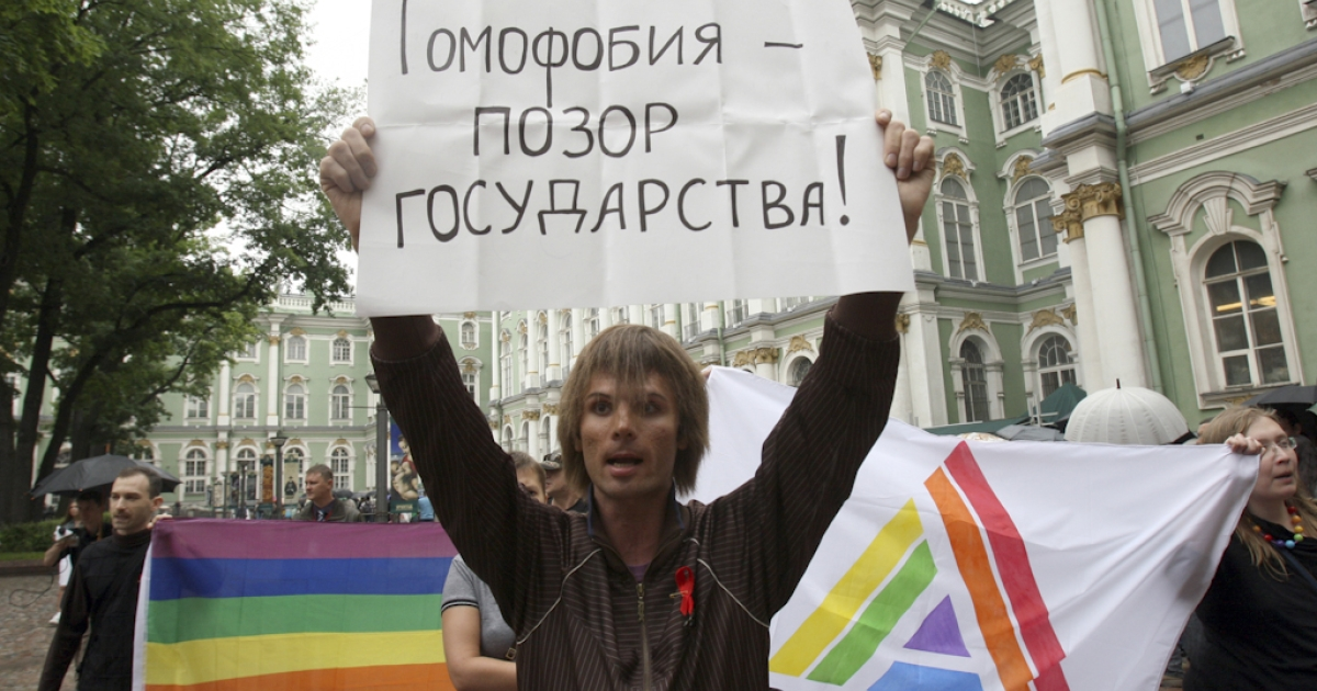 A Russian gay rights activist holds a banner reading 'Homophobia - disgrace of a country' during the gay pride protest, near the Hermitage Museum, in Saint Petersburg on June 26, 2010. Five gay rights activists were arrested today during the protest. Using similar tactics to a gay rights protest in Moscow last month, the protestors tried to outwit the security forces by only revealing the location of the demonstration at the last moment.</p>