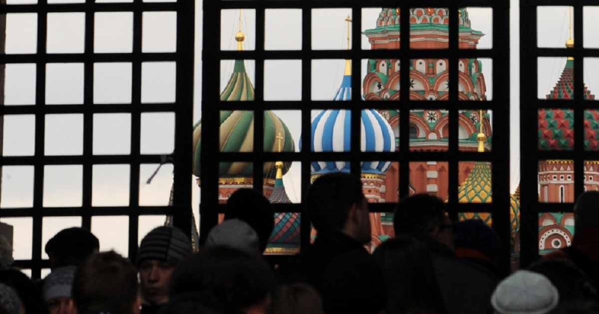 Russian opposition activists stand behind the closed entrance to the Red Square in Moscow.  About 300 people were planning to hold a silent rally there, wearing their symbol: the white stripe.</p>
