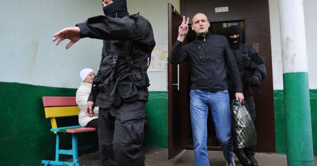 Ultra-left opposition leader Sergei Udaltsov flashes the V-sign for victory as he follows masked Interior Ministry officers taking him in for questioning after the search of his home in Moscow, on Oct. 17, 2012. Russian investigators launched a criminal case against Udaltsov, accusing him of plotting mass riots after he was featured in a documentary claiming he was planning a coup.</p>