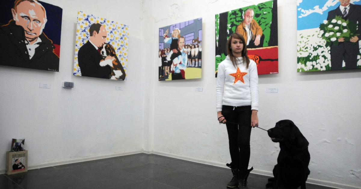 A girl with a dog stands in front of the paintings by artist Alexei Sergiyenko at his exhibition 'President. The kindest person' marking the 60th birthday of Russia's President Vladimir Putin at the Flacon design workshop in Moscow, on October 7, 2012. Putin turned 60 today.</p>