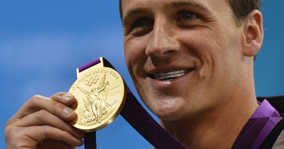 US swimmer Ryan Lochte poses on the podium with his gold medal after winning the men's 400-meter individual medley swimming event at the London 2012 Olympic Games on July 28, 2012.</p>