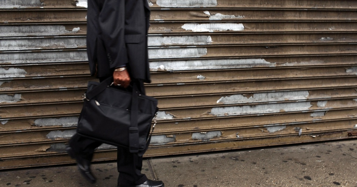 A man walks by a shuttered store in an economically depressed neighborhood on September 28, 2010 in the Brooklyn borough of New York City.</p>