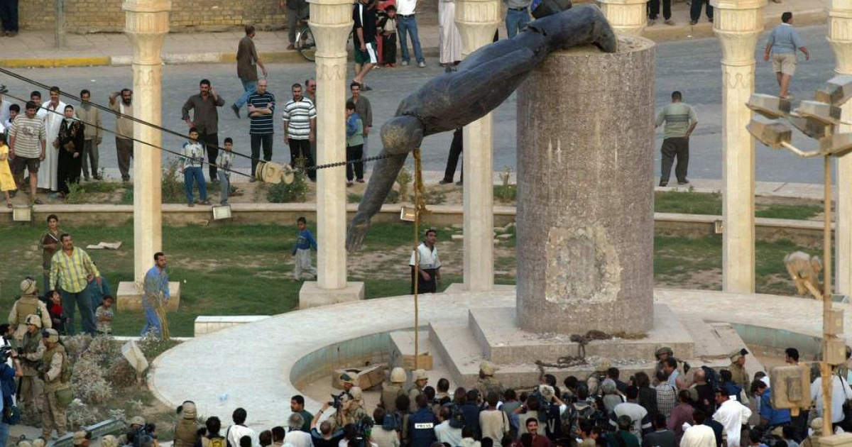 Iraqis watch a statue of Iraqi President Saddam Hussein falling in Baghdad's al-Fardous (paradise) square 09 April 2003.</p>