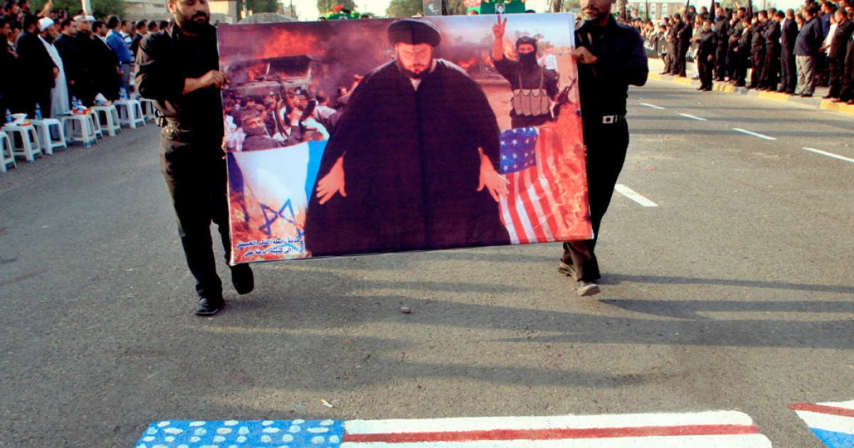 Followers of radical Shiite cleric Moqtada al-Sadr hold up a poster of their leader as they march on a US flag during a 2007 rally in Basra, Iraq.</p>