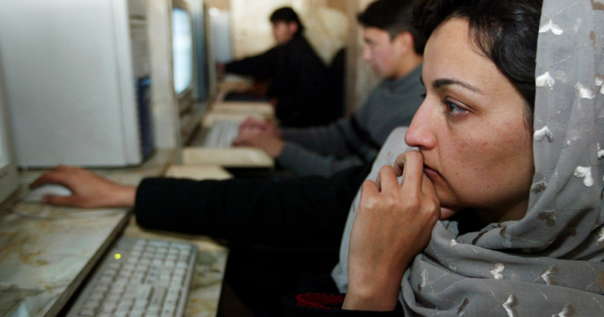 A woman uses a computer at an Internet cafe in Afghanistan.</p>