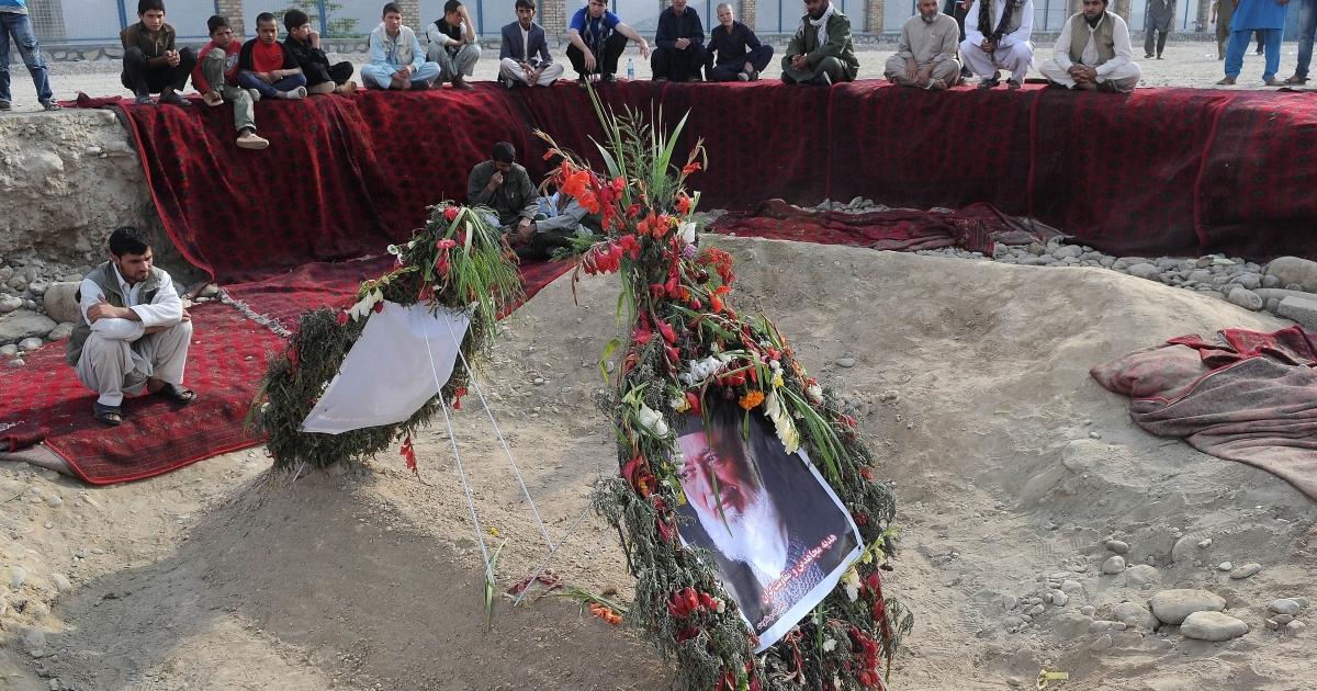 Afghan men sit over the grave site of slain Afghanistan High Peace Council and former president Burhanuddin Rabbani at the Wazir Akbar Khan hilltop over looking Kabul on September 23, 2011.</p>