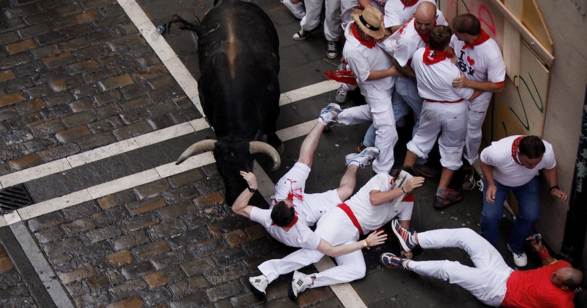 A Miura fighting bull collides with a runner along the Estafeta Street on the third day of the San Fermin running of the bulls on July 8, 2012 in Pamplona, Spain.</p>