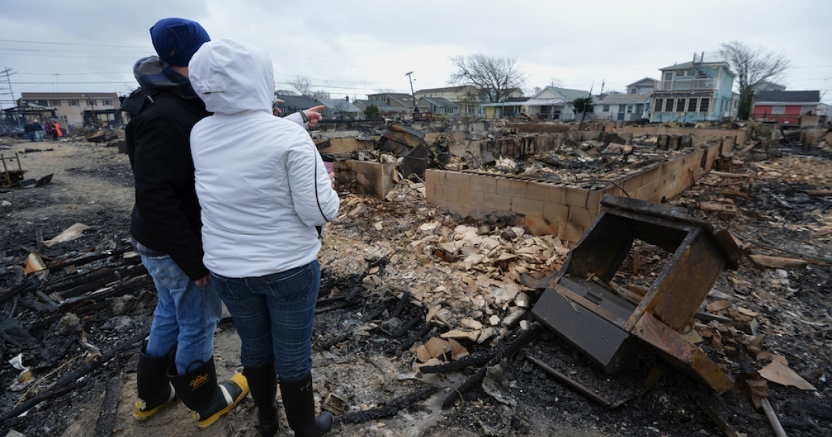 People view damage in a neighborhood in the Breezy Point area of Queens in New York on October 30, 2012 after fire destroyed about 80 homes as a result of Hurricane Sandy which hit the area October 29.</p>