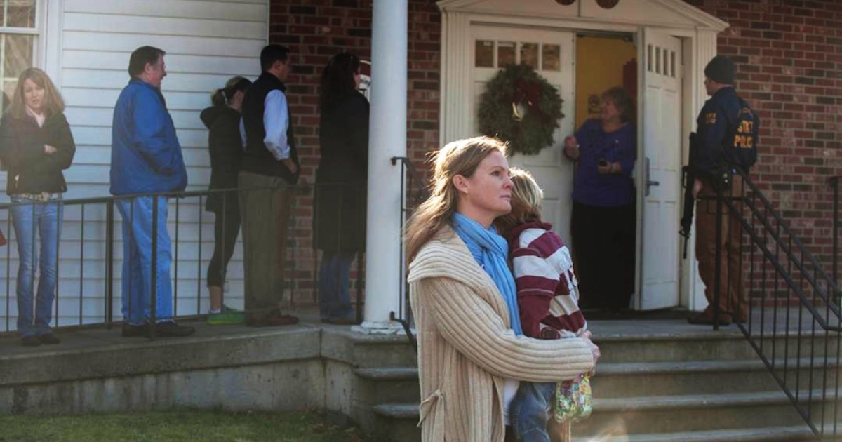 A woman holds a child as people line up to enter the Newtown Methodist Church near the the scene of an elementary school shooting on December 14, 2012 in Newtown, Connecticut.</p>