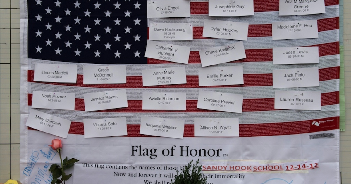 Names of victims are displayed on a flag in the business area December 16, 2012 in Newtown, Connecticut.</p>