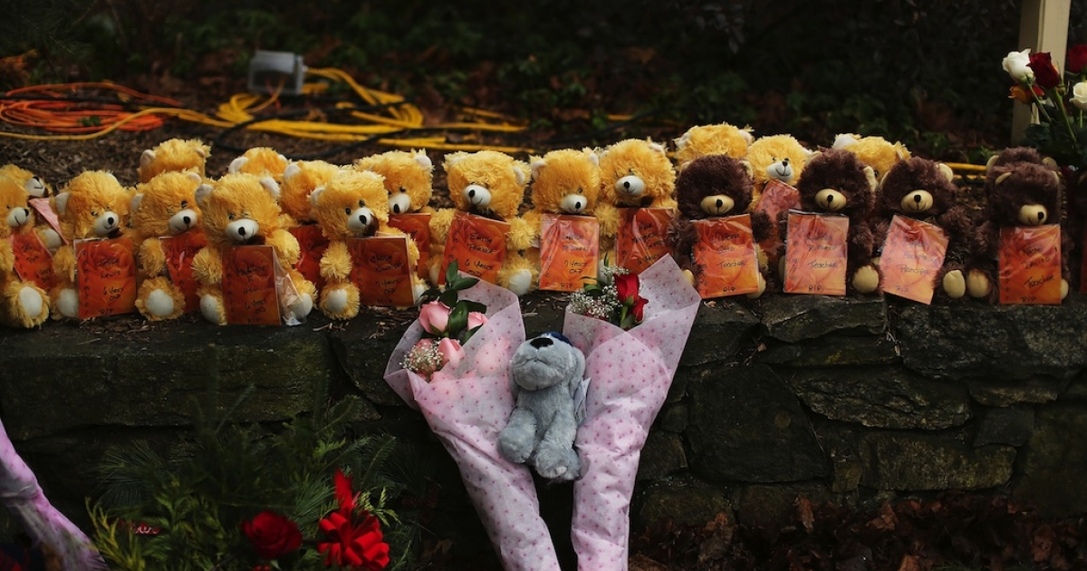 Teddy bears and flowers, in memory of those killed, are left at a memorial down the street from the Sandy Hook School December 16, 2012 in Newtown, Connecticut.</p>
