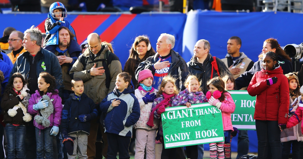 Family members of Sandy Hook Elementary School stand on the field for the National Anthem for the game between the New York Giants against the Philadelphia Eagles at MetLife Stadium on December 30, 2012 in East Rutherford, New Jersey.</p>