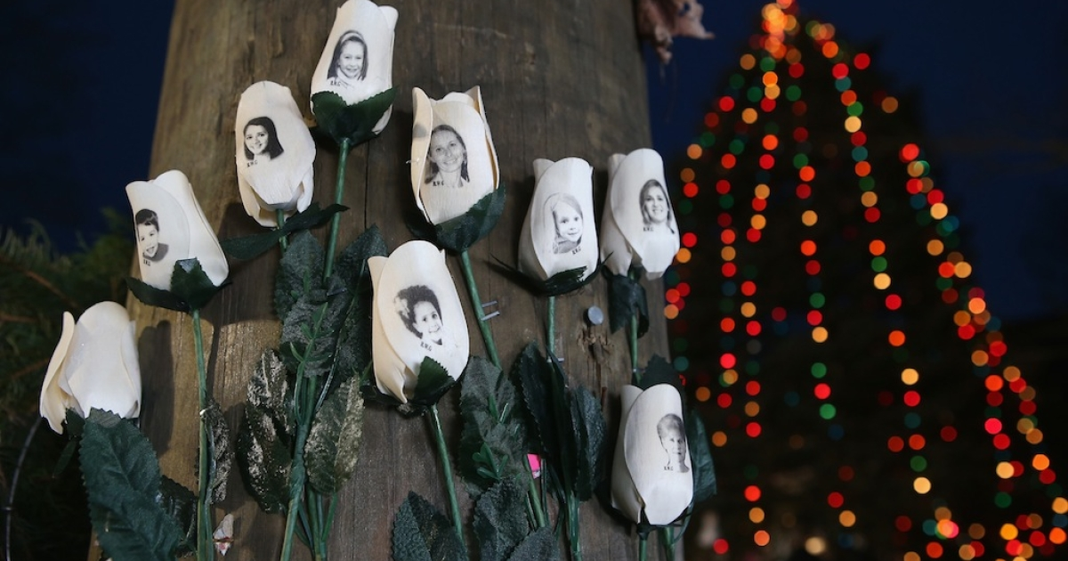 White roses with photos of victims of last Friday's mass shooting hang at a streetside memorial in Newtown, Connecticut.</p>
