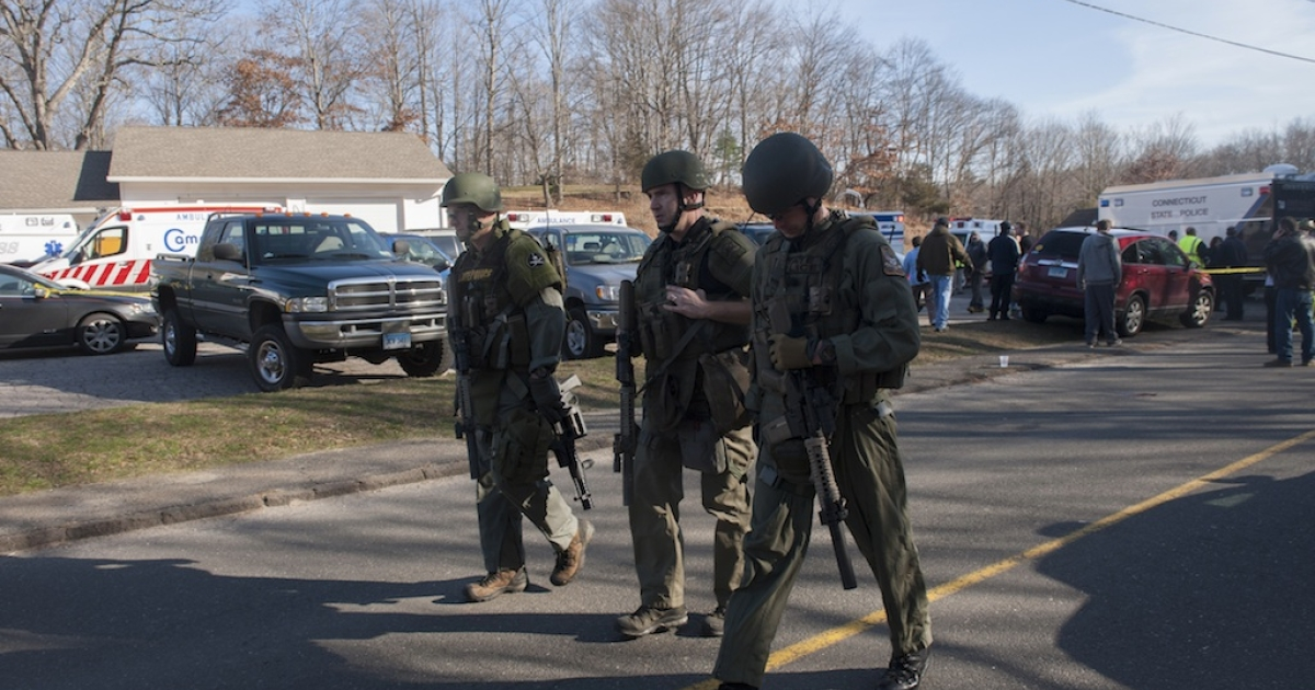 Connecticut State Police walk near the scene of an elementary school shooting on December 14, 2012 in Newtown, Connecticut.</p>