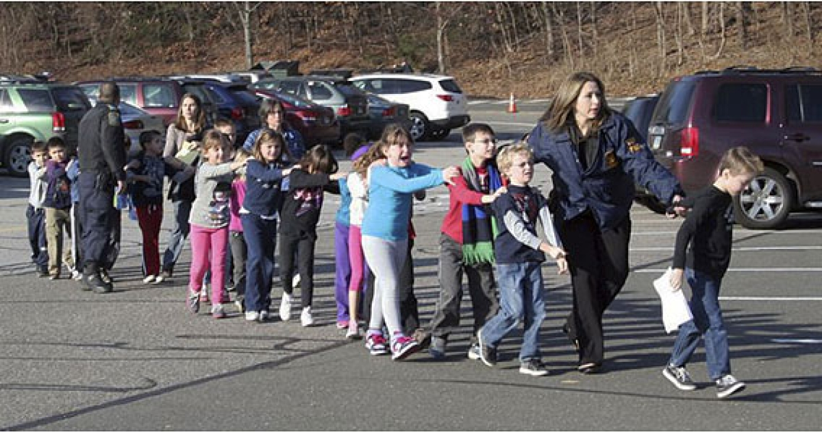 In this photo provided by the Newtown Bee, Connecticut State Police lead children from the Sandy Hook Elementary School in Newtown, Conn., on Friday, Dec. 14, 2012.<br /> Photograph by Shannon Hicks, Newtown Bee.</p>