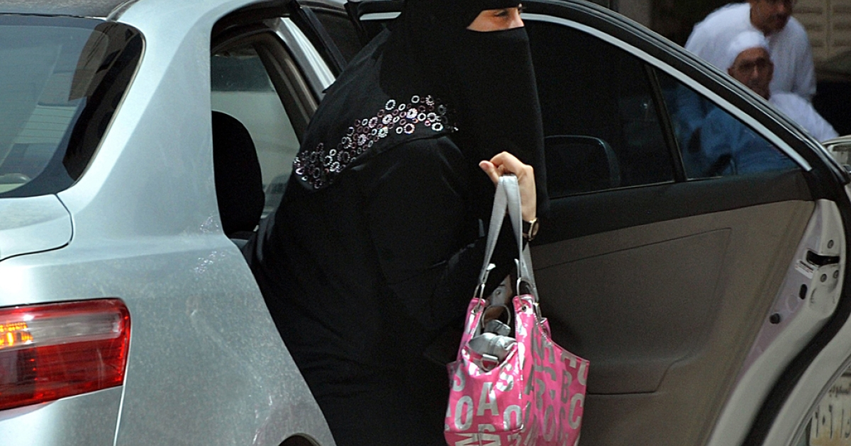 A Saudi woman gets out of a car after being given a ride by her driver in Riyadh.</p>