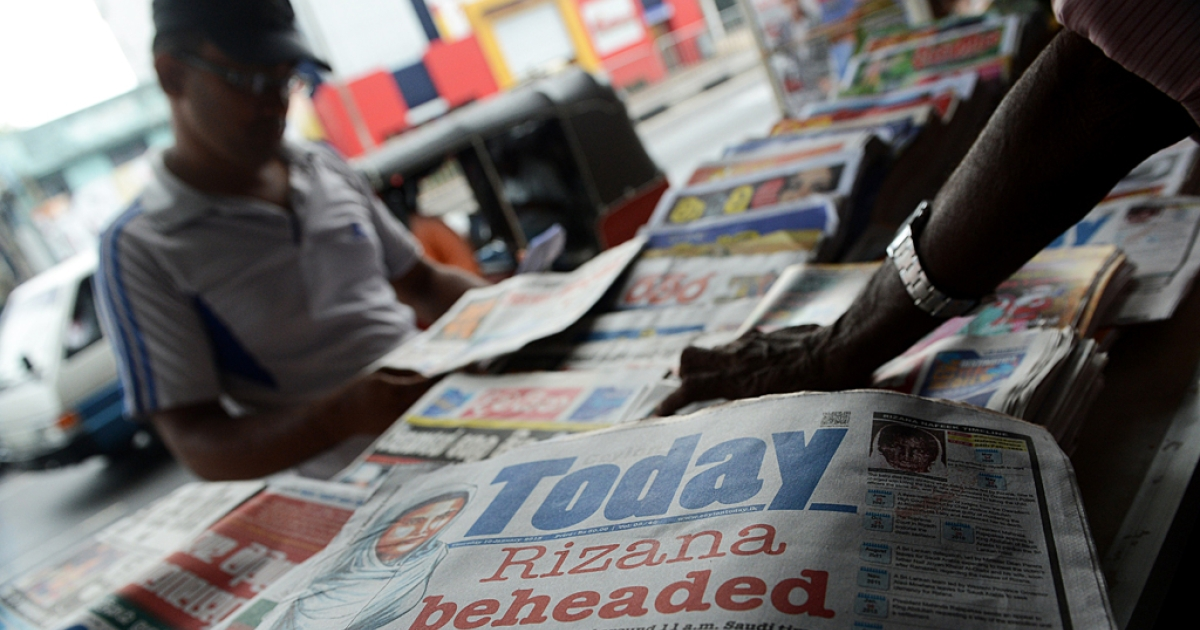 A Sri Lankan vendor displays the front page of daily newspapers in Colombo on Jan. 10, 2013.</p>