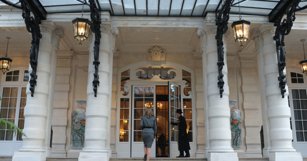 A groom opens the door of the luxury Shangri-La Hotel in Paris.</p>