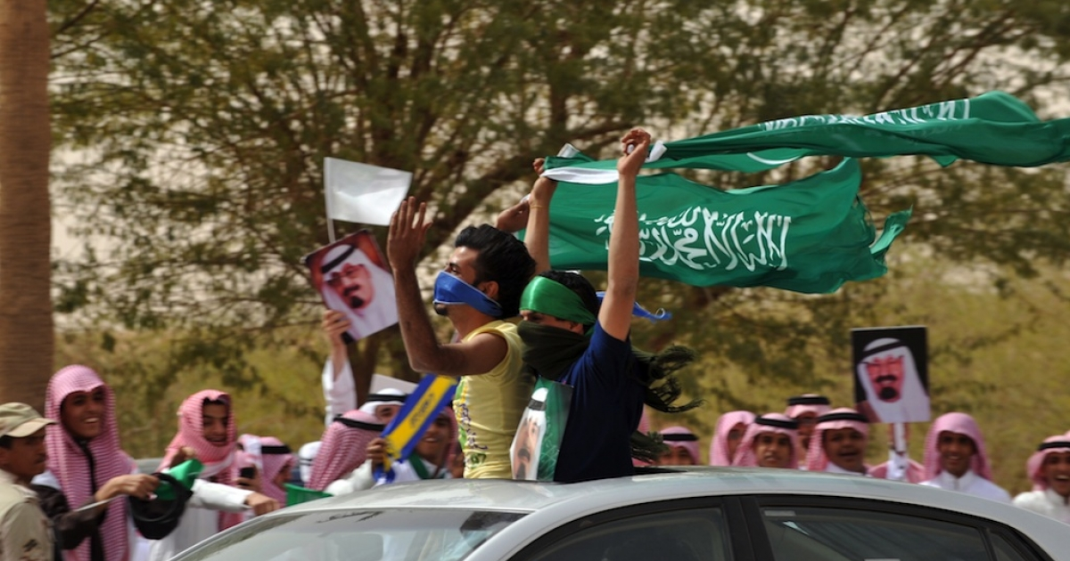 Saudi youth wave their national flag as they celebrate the return of King Abdullah bin Abdul Aziz in the Saudi capital Riyadh on Feb. 23, 2011.</p>