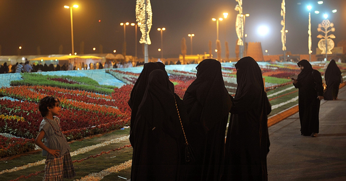 Saudi women gather in front of a carpet made of over 135,000 flowers at the Riyadh Spring Festival in the Saudi capital on April 15, 2011.</p>